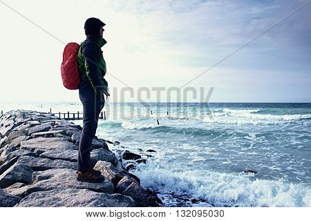 Tall hiker in dark sportswear with sporty backpack in raincoat on beach horizon with blue sky with clouds. Magic windy day. Vivid and vignetting effect