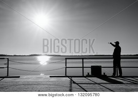 Man On Wharf Construction And Photograph Morning Sea. Tourist With Smart Phone Above Smooth Water
