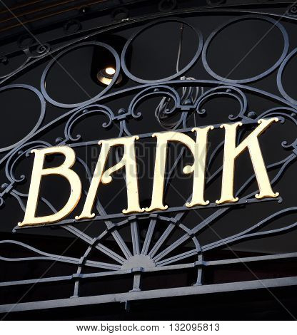 Old fashioned bank sign with ornamental wrought iron and golden letters. Building exterior of a bank. Finance symbol.