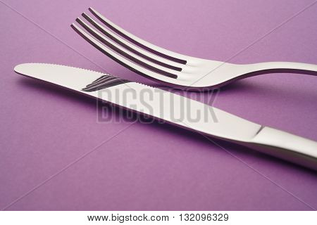 Knife and fork detail over a purple background. Cutlery. Horizontal