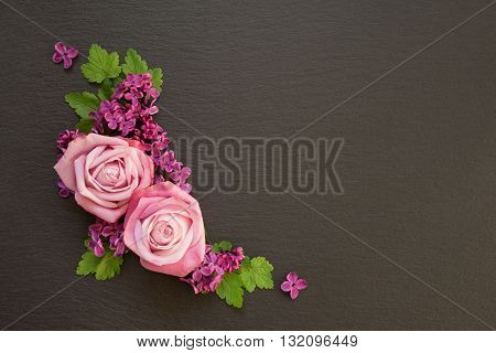 Decorative composition consisting of pink roses violet lilac flowers and green leaves on a black slate. Flat lay top view overhead view