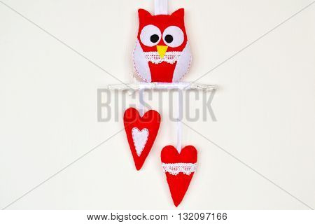 Red and white felt owl on wood branch, 2 hearts. Original composition for Valentine's Day