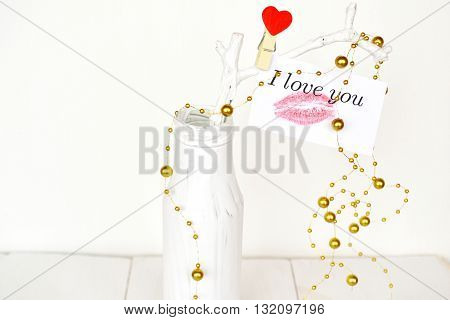 White vase with branch, words I love you. Female kiss trace created by lipstick