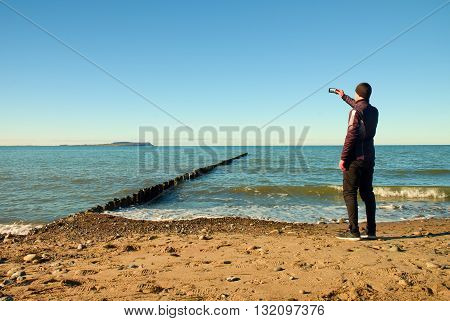 Tall Man Hold Cellphone, Take Picture Of Autumn  Sea Scenery At Breakwater.