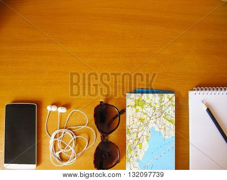 travel concept flay lay, sunglasses, map, headphones, phone, pencil, copybook, table, wooden surface