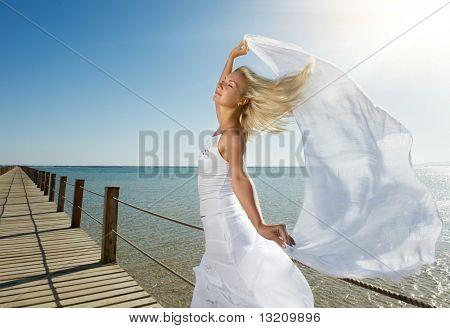 Mujer rubia con rebozo blanco relajante cerca del mar