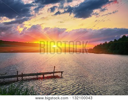 Wooden dock pier on a lake in the evening. Dramatic sunset