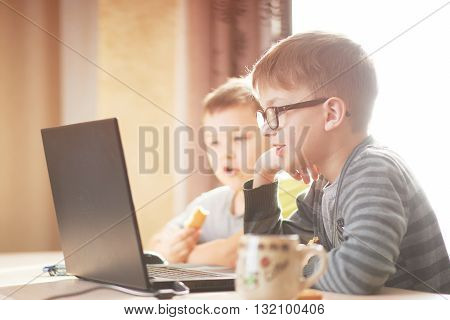 two boys play on a laptop boy t-shirt happy boy playing on a computer laptop, two brothers work there playing on the computer