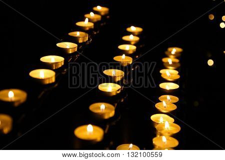 Church candle in a row. Abstract candles background. Golden light of candle flame.