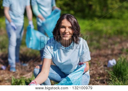 volunteering, charity, cleaning, people and ecology concept - happy woman and group of volunteers with garbage bags cleaning area in park