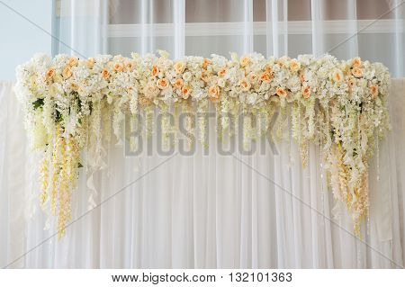 Beautiful wedding arch decorated with pink and white flowers indoors.