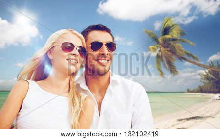 summer holidays and dating concept - happy couple in sunglasses at maldives beach