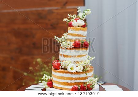 three-tiered wedding cake with strawberries on table.