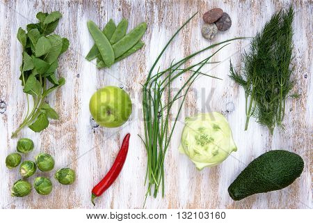Set of green vegetables on white painted wooden background: kohlrabi, avocado, brussels, sprouts, apple, pepper, green onion, pea, pods, dill, basil.
