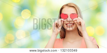love, romance, valentines day and people concept - smiling young woman or teenage girl with red heart shapes on eyes over summer green lights background