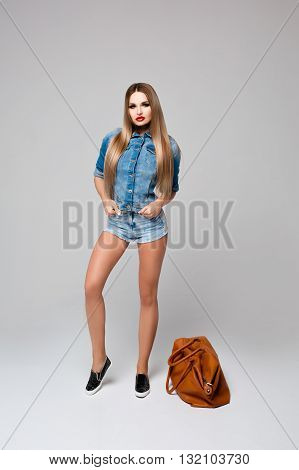 Beautiful young woman with long glossy hair, denim outfit, hands in pockets, about toe leather red tote bag. Stylish makeup, shirt, shorts, long legs