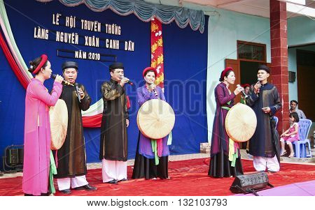 Bac Ninh, Vietnam - Mar 24, 2010: Vietnamese popular artist in traditional costume singing traditional melody called Quan Ho Bac Ninh in occasion of a local folk festival.