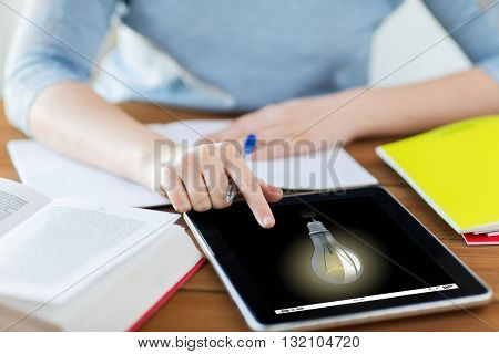 business, education, idea, technology and people concept - close up of student woman with light bulb on tablet pc computer and notebook at home