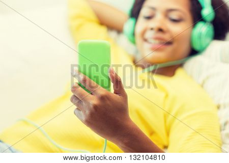 people, technology and leisure concept - close up of happy african american young woman lying on sofa with smartphone and headphones listening to music at home
