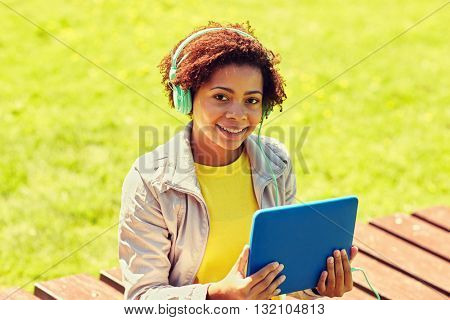 technology, lifestyle and people concept - smiling african american young woman or teenage girl with tablet pc computer and headphones listening to music in summer park
