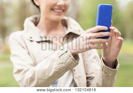 drinks, leisure, technology and people concept - smiling woman taking picture or selfie with smartphone in park