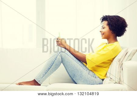 people, technology and leisure concept - happy african american young woman sitting on sofa with smartphone at home