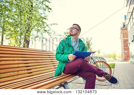 people, inspiration, technology and lifestyle - happy young hipster man with tablet pc computer sitting and thinking on bench in city
