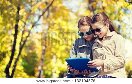 people, children, technology, season and friendship concept - happy little girls in sunglasses with tablet pc computer over autumn park background