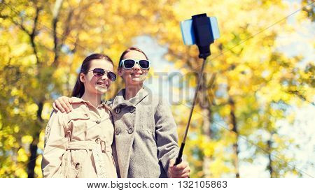 people, children, friendship and season concept - happy girls taking picture with smartphone on selfie stick over autumn park background