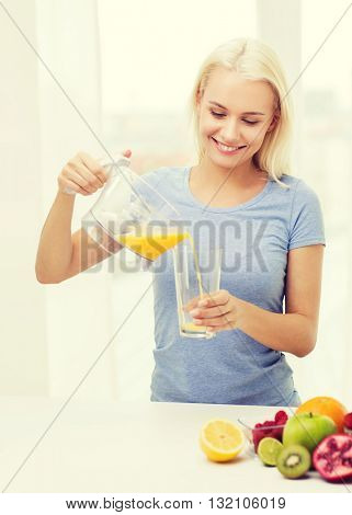healthy eating, vegetarian food, dieting and people concept - smiling woman pouring fruit orange juice from jug to glass at home