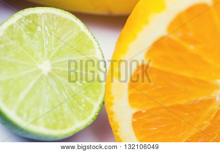 healthy eating, food, fruits and diet concept - close up of fresh juicy orange and lime