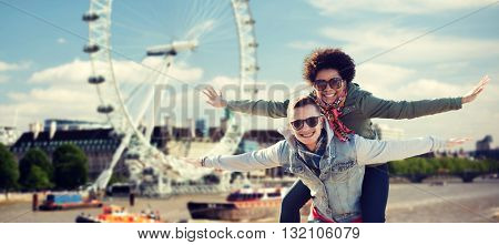 friendship, leisure, international, freedom and people concept - happy teenage couple in shades having fun over london ferry wheel background
