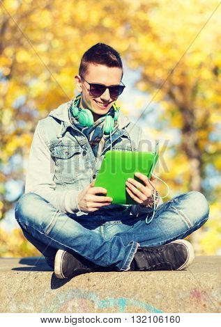 technology, lifestyle, season, music and people concept - smiling young man or teenage boy with tablet pc computer and headphones over autumn park background