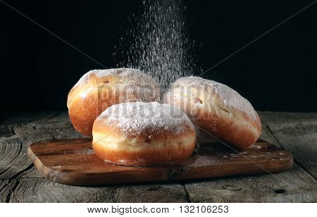 Three donut sprinkled with powdered sugar on wooden table on black background closeup. Food background