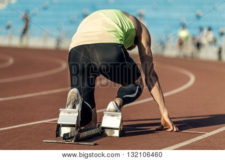 male athlete in starting blocks. running at sprint at stadium
