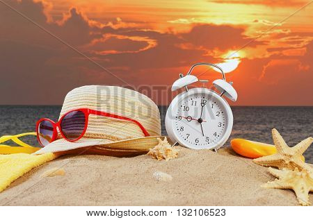 Beach accessories with alarm clock on the beach in the sand on sunset background. Summer vacation concept