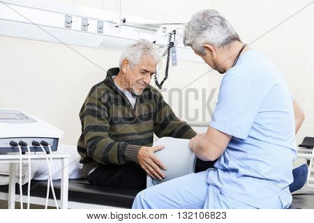 Physiotherapist Examining Senior Patient On Bed