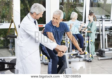 Senior Man Looking At Doctor While Cycling In Fitness Studio