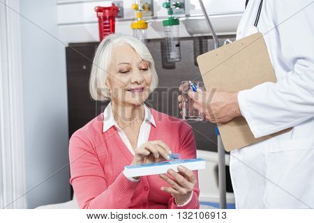 Patient Holding Medicine Organizer While Doctor Giving Her Water