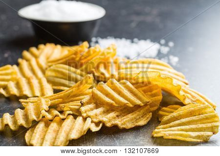 Crinkle cut potato chips on kitchen table. Tasty spicy potato chips with salt.