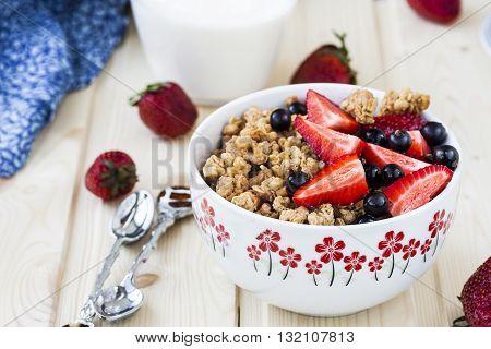 Healthy breakfast with granola milk honey and fresh berries