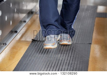 Low Section Of Senior Man Walking At Fitness Studio