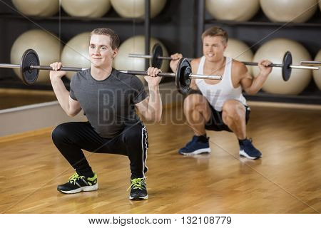 Friends Lifting Barbell While Crouching In Gym
