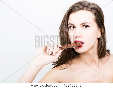 close-up portret of beautiful sexy woman with red lips eating chocolate.
