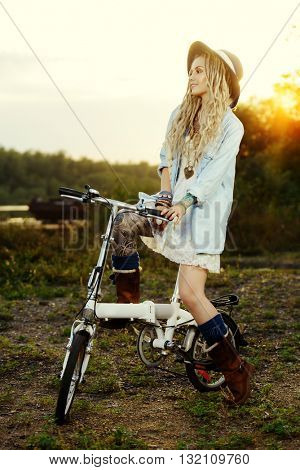 Dreamy smiling girl in boho style clothes rides a bicycle. Beauty, fashion. Summertime, sunset.