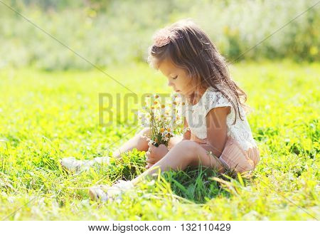 Little Girl Child Sitting With Bouquet Of Chamomiles Flowers On Grass In Summer Day