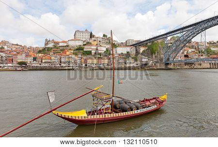 PORTO PORTUGAL - MAY 25 2016: Traditional Rabelo boat (port wine carrier) on Douro River in Porto Portugal. Dom Luis I Bridge and historical part of Porto city (UNESCO site) at the background