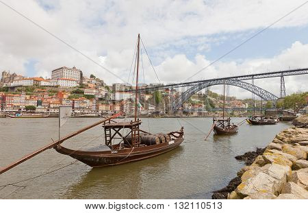 PORTO PORTUGAL - MAY 25 2016: Traditional Rabelo boats (port wine carrier) on Douro River in Porto Portugal. Dom Luis I Bridge and historical part of Porto city (UNESCO site) at the background