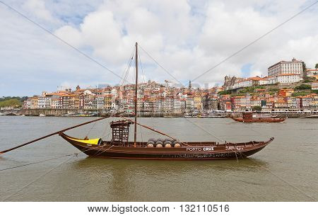 PORTO PORTUGAL - MAY 25 2016: Traditional Rabelo boat (used for port wine transportation) at Douro River in Porto Portugal. Historical part of Porto city (UNESCO site) at the background