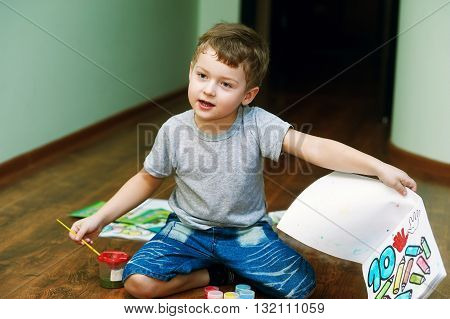 Cute little boy painting with brush , sitting on the floor of the house